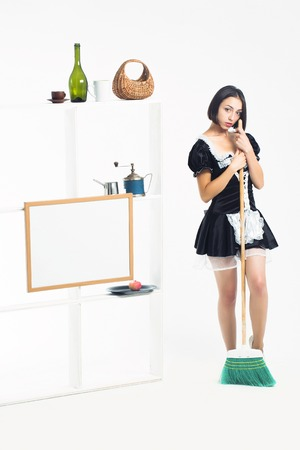 sexy maid: Young girl with pretty face in sexy beautiful black maid servant costume posing with green sweep broom near kitchenware on shelves isolated on white background Stock Photo