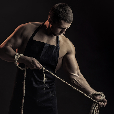 sexual anatomy: One handsome sexual strong young man with muscular body in working blue apron holding rope standing posing in studio on black background, square picture