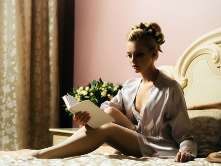negligee: Beautiful woman sensual young bride in sexy silk negligee sits on bed and reads diary in bedroom