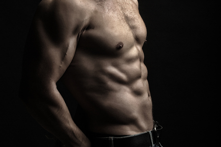 sexual anatomy: Closeup view of one handsome sexual strong young male bare chest of muscular body standing posing on studio background, horizontal picture