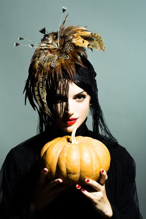 female shaman: young sexy woman or girl with red lips on pretty face in beautiful feather hat brown color as halloween or carnival holiday costume and veil holds pumpkin on grey background