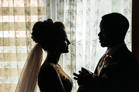 african american woman silhouette: Silhouette of bride beautiful young woman and groom handsome african American man with wedding bouquet look at each other with love on background of window Stock Photo