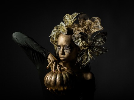 metallized: halloween golden woman or girl holding painted gold pumpkin has pretty face with makeup and body art metallized color with decorative flowers on head on black background