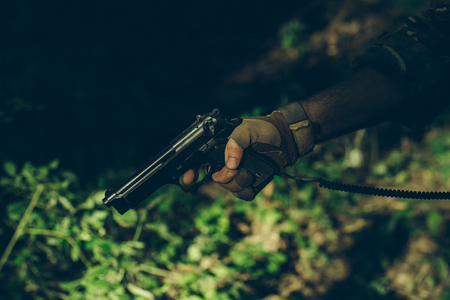 aggressiveness: Male hand in military glove with pistol holding finger on firing hammer on green grass background closeup Stock Photo
