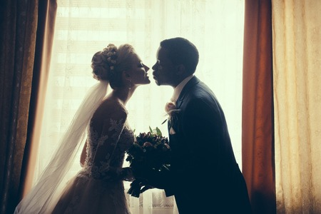 african american woman silhouette: Silhouette of bride beautiful young woman and groom handsome african American man with wedding bouquet kiss on background of window