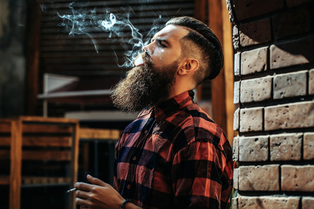 Adult man hipster with long moustache and beard on brutal handsome face fashion hair dressed in chequered shirt exhaling cigarette smoke near brick arch background indoor