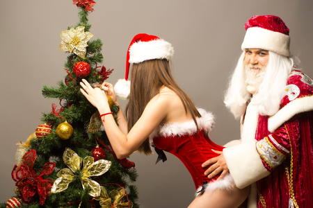 Funny man in santa or new year suit grabs pretty sexy girl decorating Christmas tree on grey wall Stockfoto