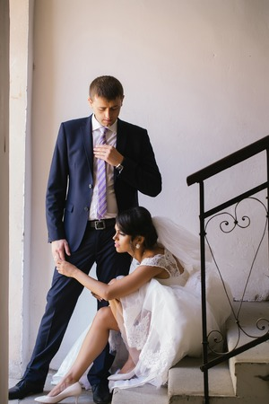 elegant staircase: Beautiful bride woman with sexy legs in white wedding dress and veil sits on staircase and holds hand of elegant groom man