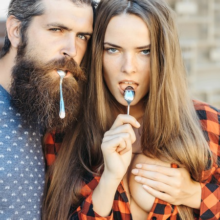 tea spoon: young couple of pretty girl with long hair and handsome bearded man hipster with beard holding metallized tea spoon outdoor
