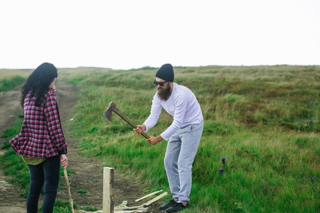Sterke man houthakker snijdt hout met vriendin mooi meisje buiten in de zomer op natuurlijke achtergrond Stockfoto