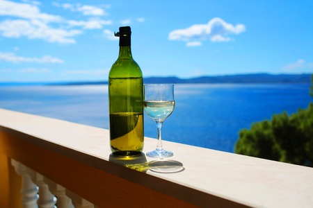 alcoholic beverage: alcoholic beverage of white wine in green bottle and glass outdoor on summer day on blue sea