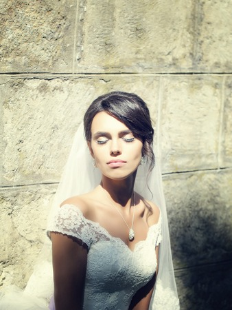 young sexy woman or girl bride with makeup on pretty face and wedding veil in hair sunny summer outdoor on stony wall background