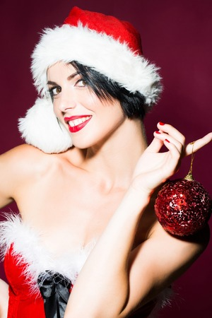 costume ball: young sexy new year woman or girl with and red lips on pretty smiling happy face in christmas santa claus hat and holiday costume holds decorative ball in studio on purple background