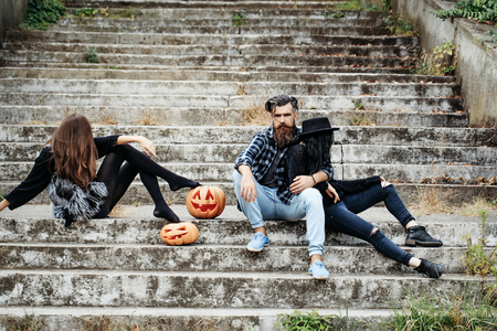 young halloween bearded man with beard and mustache and two girls in black witch hat tights and jeans sit on stony stairs with traditional autumn holiday symbol of orange spooky pumpkin outdoor Stock Photo