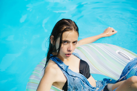 rubber ring: young sexy woman or girl with pretty face and wet hair swimming in pool on rubber ring with blue water sunny summer day outdoor