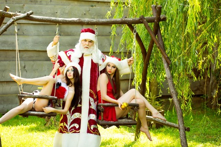Serious santa claus man in new year Christmas red costume with pretty girls in sexy dresses on swing on natural background Stock Photo