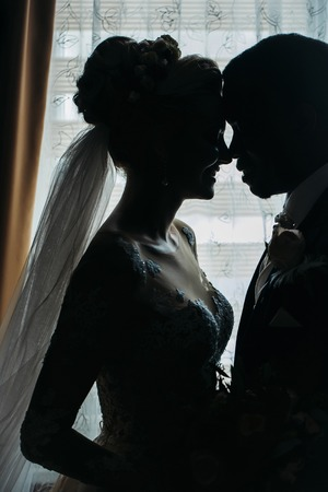married couples: Silhouette of bride beautiful young woman and groom handsome african American man share love head to head on background of window