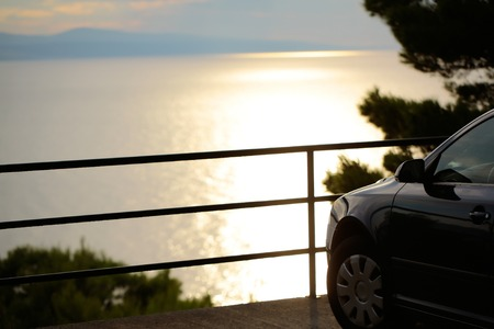 over the edge: Car parked at edge of viewpoint in mountain over sea on summer evening Stock Photo