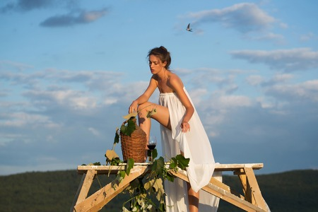 bottle of vine: Beautiful girl in white sexy dress denuded with red wine in glass wicker bottle vine and grapes on nature over blue sky Stock Photo