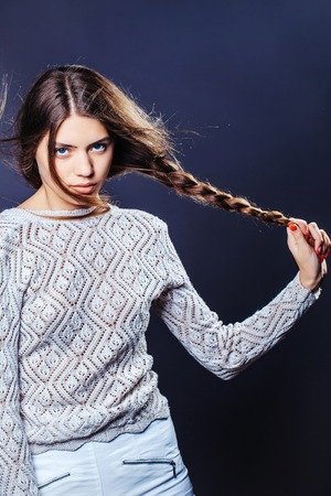 sexy sweater: Sexy fashionable girl or woman with pretty face slim model with stylish long brunette hair in white sweater and shorts in studio on grey background