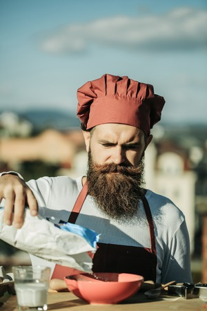 cook house: Man cook chef hipster with bearded handsome face in red uniform and hat pouring floor ingredient in bowl on blue sky and house roof background outdoor