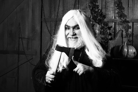 house robes: Old wizard with long hair in robe with demonic smile hold ax near finger in wooden house, black and white Stock Photo