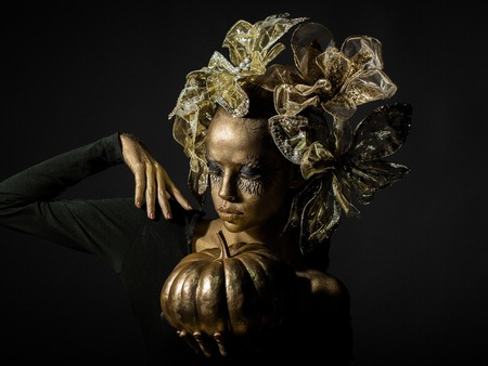 cinderella: halloween golden woman or girl holding painted gold pumpkin has pretty face with makeup and body art metallized color with decorative flowers on head on black background