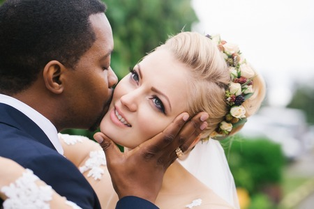 gently: Loving groom african American man gently kisses face of beautiful bride blond woman with elegant hairstyle and wreath outdoors on wedding day