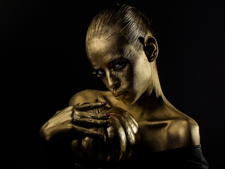 body paint sexy: halloween golden woman or girl holding painted gold pumpkin has pretty face with makeup and body art metallized color with bare shoulders on black background Stock Photo