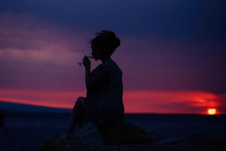 여자 또는 여자의 여자 또는 여자와 구름과 바다 또는 바다와 극적인 어두운 하늘을 통해 야외 와인 글라스의 꽤 섹시 한 여성 실루엣 저녁 또는 황혼