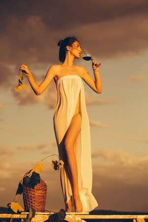 Pretty young girl or woman in white sexy dress denuded with red wine in glass wicker bottle vine and grapes on nature over blue sky with sunset