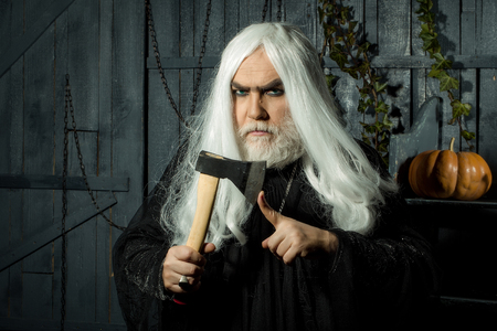 hatchet man: Angry man witch in black robe with white long hair and beard hold hatchet near finger in wooden house