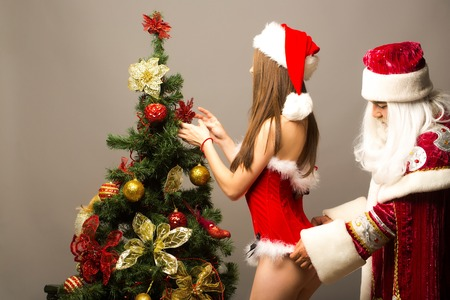 Santa claus man touches fur on sexy red dress of pretty girl decorating Christmas tree on grey wall