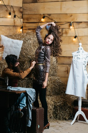 customer tailor: Bearded man tailor or dressmaker takes measurements from pretty girl customer or sexy model with curly brunette hair in rustic workshop