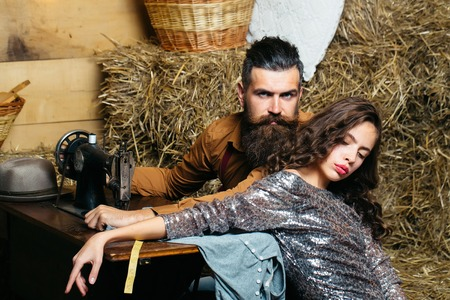 customer tailor: Bearded man tailor or dressmaker and pretty girl customer or sexy model with curly brunette hair in dress pose near vintage sewing machine in rustic workshop