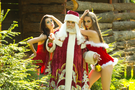 Serious santa claus man in new year red costume and pretty girls in sexy dresses pose near Christmas tree on natural background
