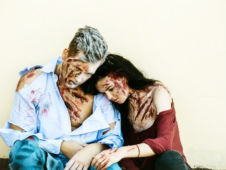 Halloween zombie couple of handsome man or war soldier and bloody young woman with wounds and red blood sit on beige wall Фото со стока