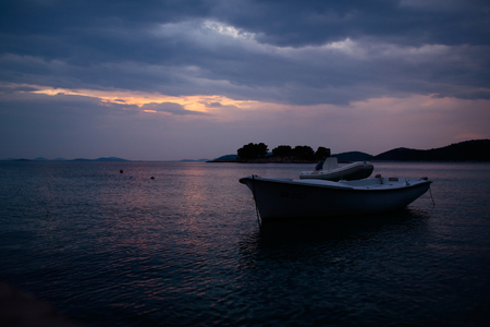inshore: White rowboat and rubber boat with motor at anchor in calm blue sea water inshore after sunset on beautiful evening seascape