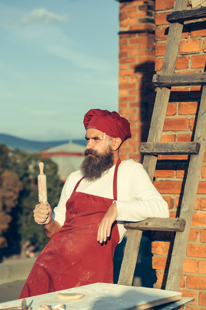 nudelholz: Man chef cook hipster in red hat and apron and white uniform with long beard on handsome face holding wooden rolling pin in hand leaning on ladder near brick wall outdoor