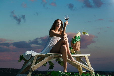 pretty girl in white sexy dress denuded gorgeous body with red wine glass wicker bottle and vine on evening nature over blue sky
