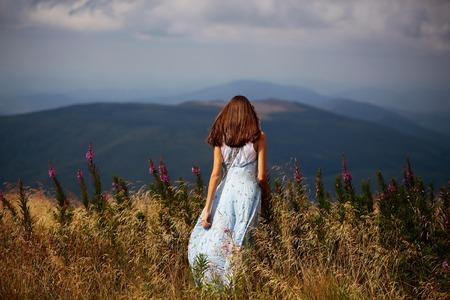 Pretty cute brunette woman or girl stands back in blue dress waving on wind outdoor on beautiful landscape