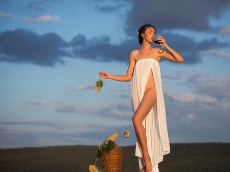 파란 하늘을 통해 자연에 빨간색 유리 고리 버들 병 포도 나무에서 와인과 포도 무 결함 흰색 섹시 드레스에 꽤 젊은 여자 또는 여자