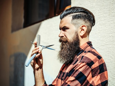 Adult man hipster with thoughtful handsome face brutal long beard and moustache fashion hair holding barber razor and scissors posing in profile on light wall background outdoor