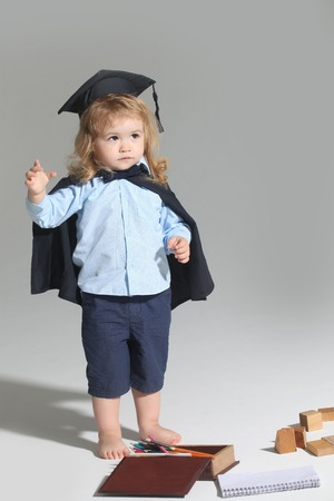 Small boy child with long blond hair in blue shirt black graduation gown and cap playing with pencil box isolated on white background Imagens