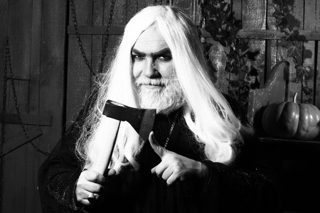 hatchet man: Angry man witch in robe with long hair and beard hold hatchet near finger in wooden house, black and white
