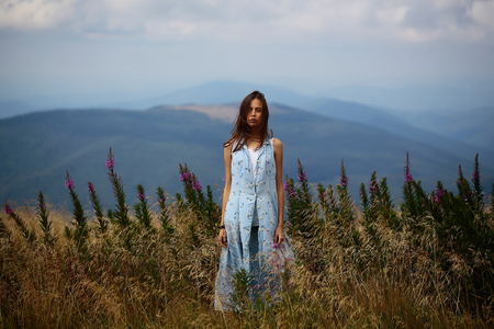 the stands: Pretty cute sexy brunette woman or girl in blue dress stands straight outdoor on beautiful landscape Stock Photo