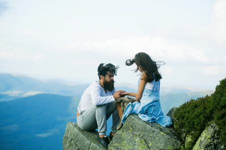 romantic man: Romantic couple of pretty woman or girl and handsome bearded man with beard on cliff on summer day over mountain tops with blanket Stock Photo
