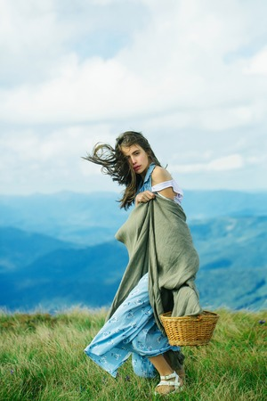 Pretty cute sexy woman or girl in blue dress and brunette hair waving in wind stay with basket and veil on outdoor on beautiful landscape on blue sky background