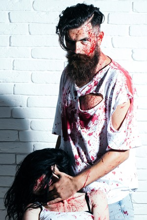 Bearded man zombie bloody hipster and creepy girl young woman with wounds and red blood on brick wall Stock Photo