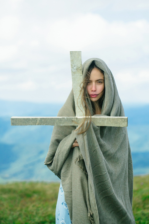 quietness: Pretty sexy young cute girl or woman with serious face wrapped in veil holding cross on meadow Stock Photo